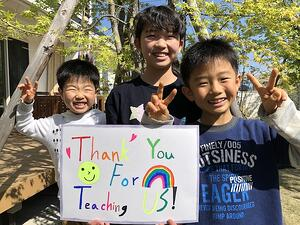 three young boys holding a colorful thank you sign for their teacher