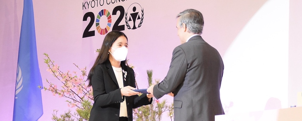 A girl handing documents to a man on the stage at the UN Kyoto Congress