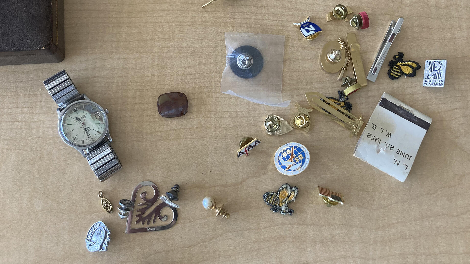 An old watch, a matchbook from 1952, lapel pins, old pendants, and trinkets are scattered over a wooden desk