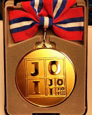 A round, gold medal with a red, white, and blue ribbon sitting in a brown velvet box. The medal reads JOI