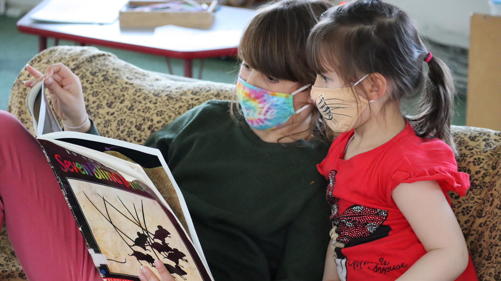 An older child in a green sweatshirt and tie-dye mask reads a picture book to a younger child in a red T-shirt and tiger mask as they sit on a small sofa