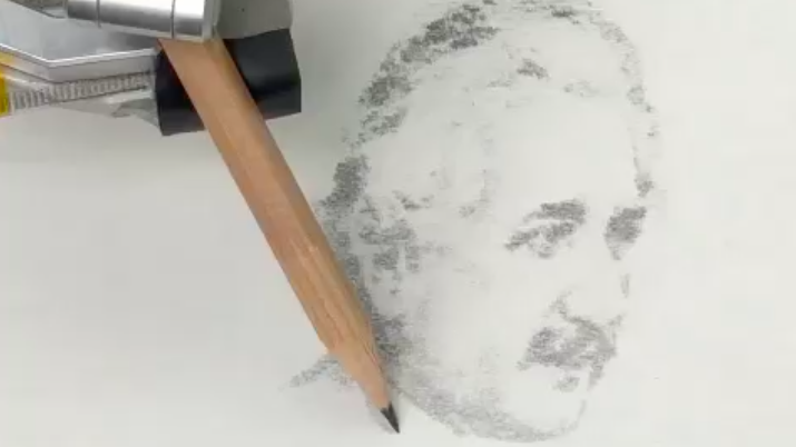 A robotic arm holds a pencil and is sketching a picture of Einstein using dark and light shading.